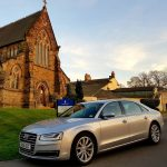 Silver Audi car outside a church